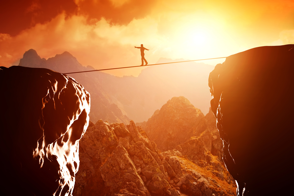 image of a person walking a tightrope strung between two cliffs, set against a sunset. emotional balance, struggle.