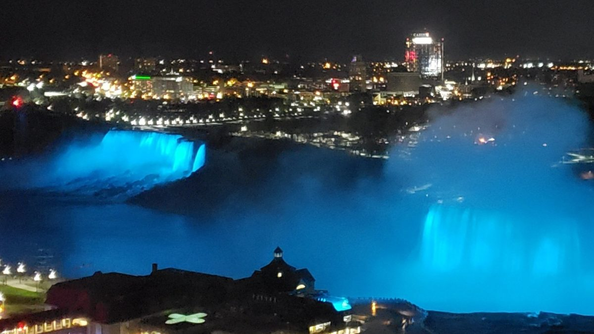 night shot with view of Niagara Falls lit up by lights