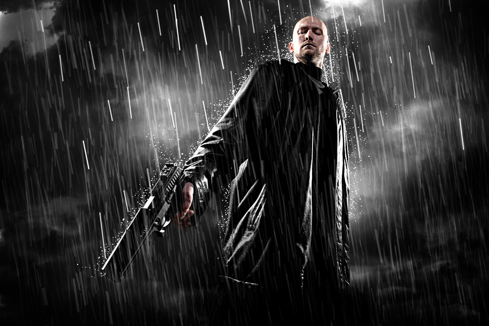 man with a gun, looking down, set against a dark stormy night.